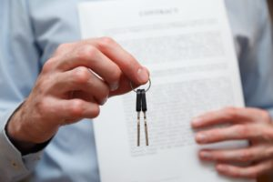 Businessman offering a key with contract. Rental agreement with contract