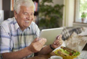 Elder man using a digital tablet at the table